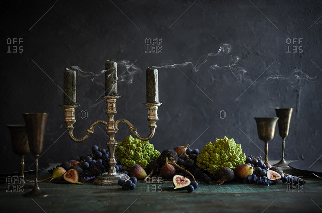 A gorgeous, creepy halloween tablescape with rustic candelabra with blown out candles. Vegetable spread across table with romanesco broccoli, concord grapes, figs and black radishes.