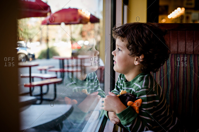 Little boy looking out of a restaurant window