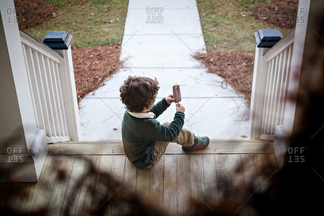Boy eating chocolate ice pop on the front porch