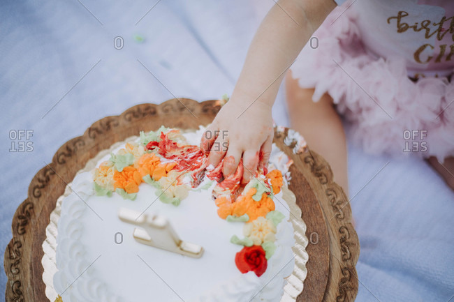 Overhead view of baby grabbing cake frosting on her birthday
