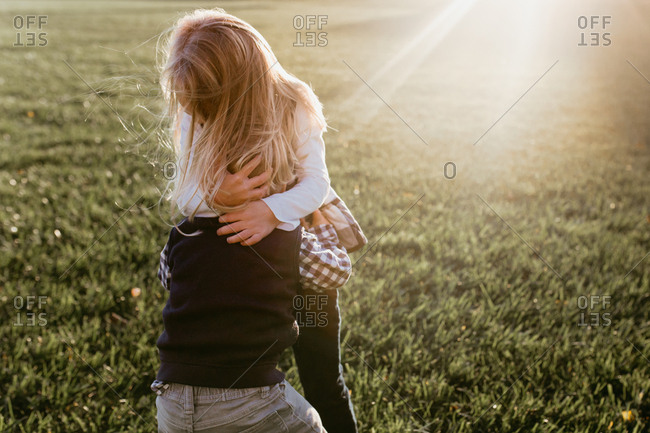 Two siblings hugging in a grassy field