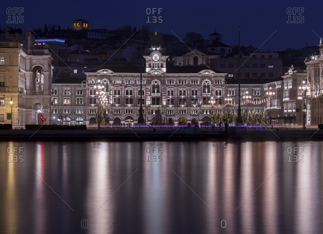 Trieste, Italy - December 13, 2016: The Town Hall reflected on the waterfront of Trieste at Christmas time