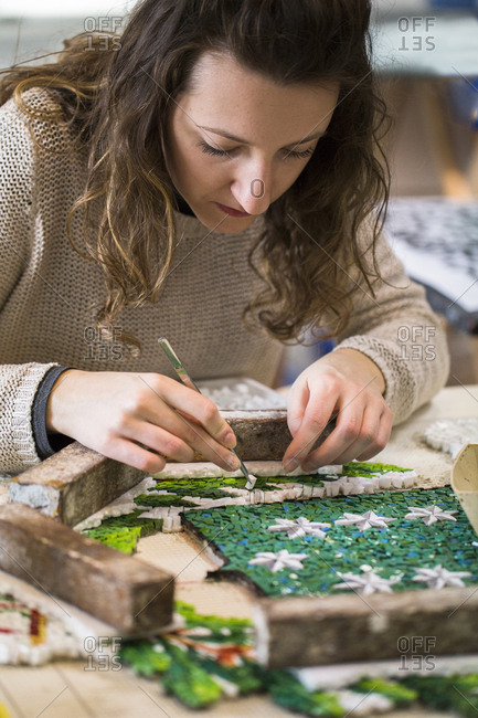 Spilimbergo, Italy - January 16, 2017: Pordenone, Italy - January 16, 2017: Young girl learns the art of mosaic in the oldest Mosaic School of Friuli