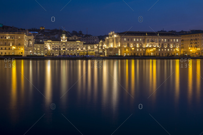 Buildings and Government palace on the waterfront of Trieste at night at Christmas time, Italy