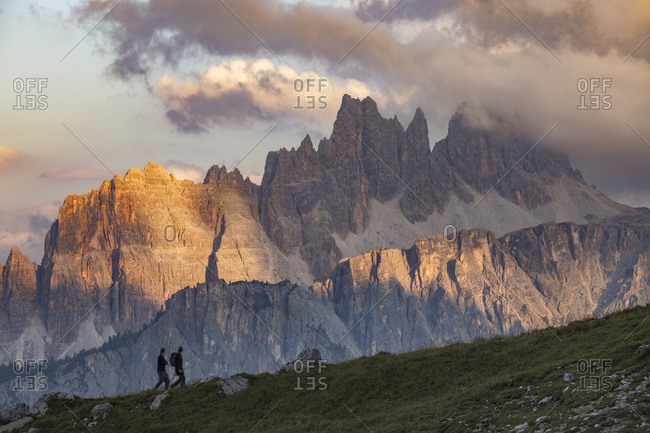 Two trekkers admire the sunset on the Croda Da Lago Mount, Cortina d'Ampezzo, Dolomites, Italy