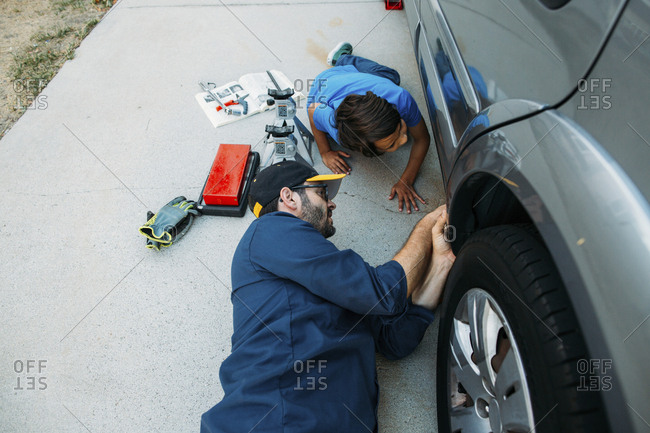High angle view of father teaching son to repair car at driveway