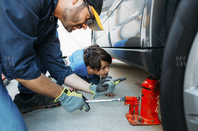 Father guiding son while using car jack to repair car at driveway