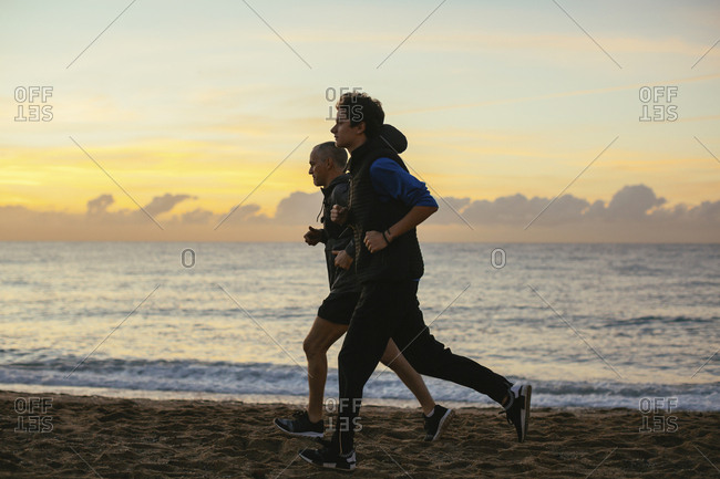 Determined father and son jogging at beach against cloudy sky during sunset