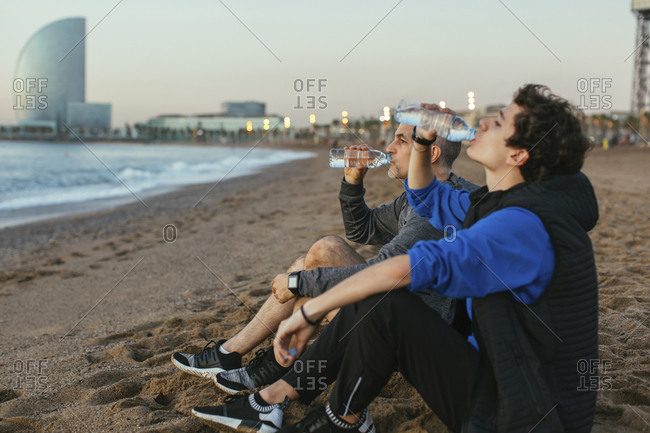 Father and son drinking water while sitting against Hotel Vela at beach