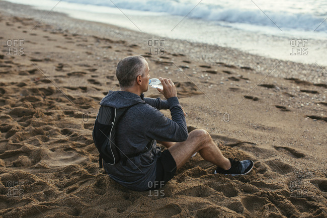 High angle view of man drinking water while sitting at beach