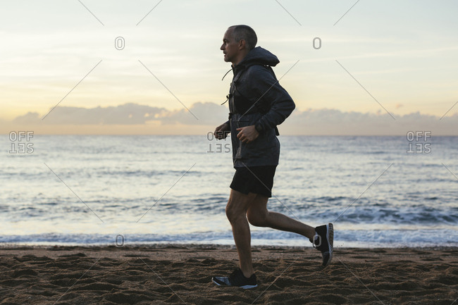 Side view of man jogging at beach against sky during sunset