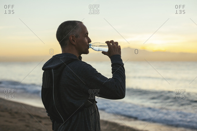 Side view of man drinking water while standing at beach during sunset