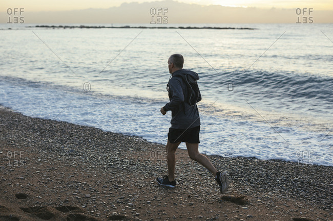 High angle view of man jogging on shore at beach