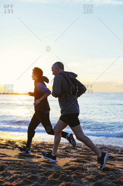 Side view of father and son jogging on shore at beach against sea during sunset