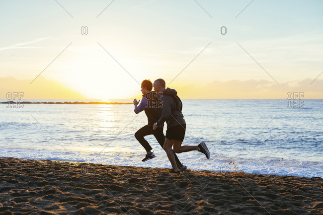 Full length of father and son jogging on shore at beach against sky