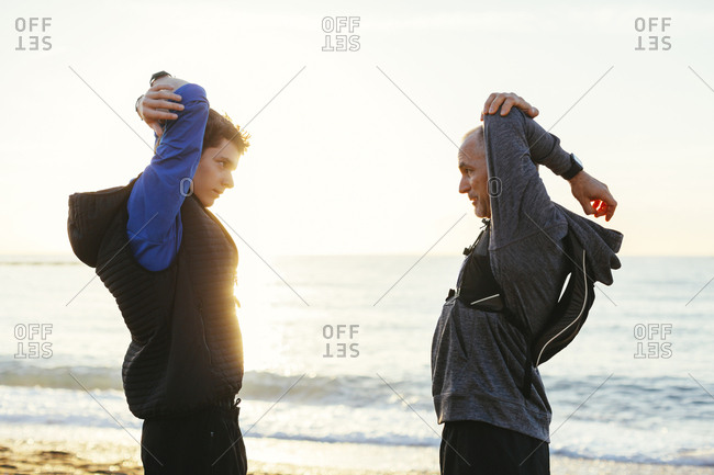 Side view of father and son stretching arms while standing face to face at beach against clear sky