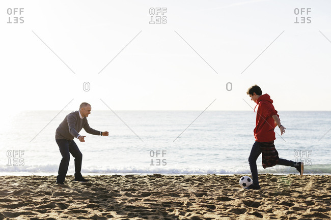 Son kicking soccer ball while father defending at beach against clear sky