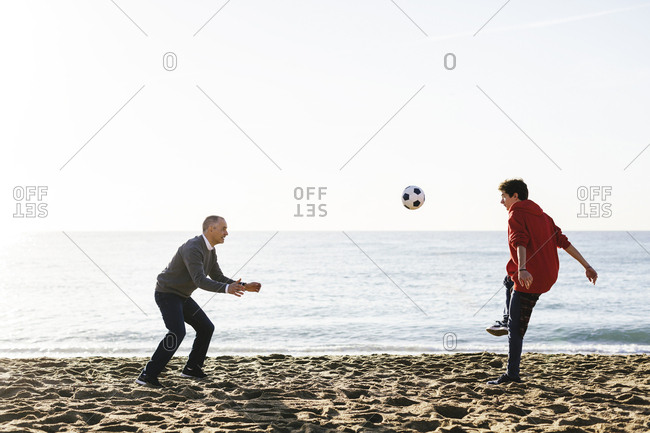 Playful son kicking soccer ball while father defending at beach against clear sky