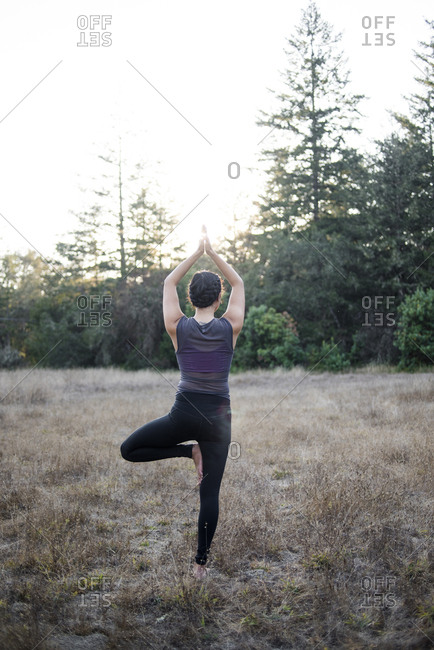 Rear view of woman practicing tree pose at field