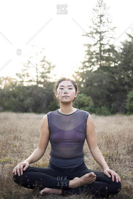 Portrait of confident woman with cross-legged practicing yoga at field