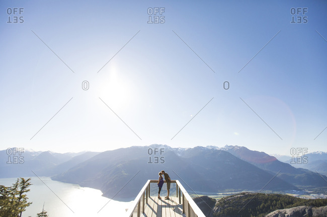 High angle view of couple kissing while standing against mountains and clear sky at observation point during sunny day