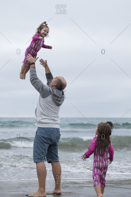 Daughter looking at playful father throwing sister in air while standing on shore against sky