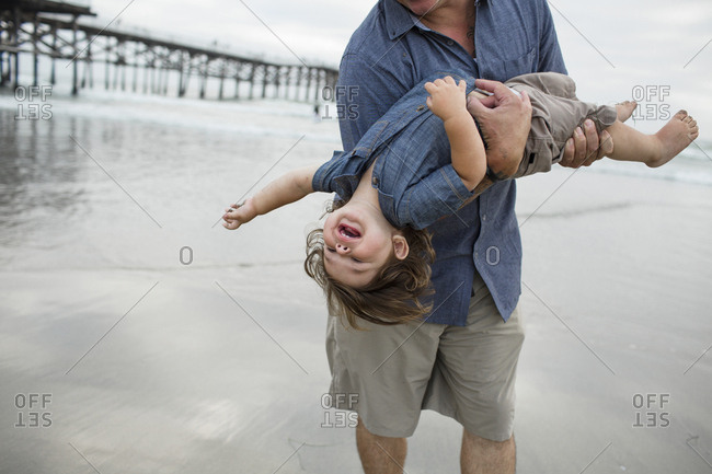 Midsection of playful father carrying son while playing on shore at beach