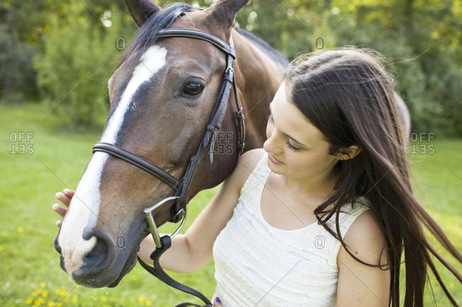 Teenage girl petting horse at field