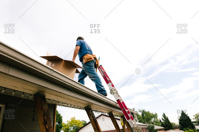 Construction worker climbing on a roof to install solar panels