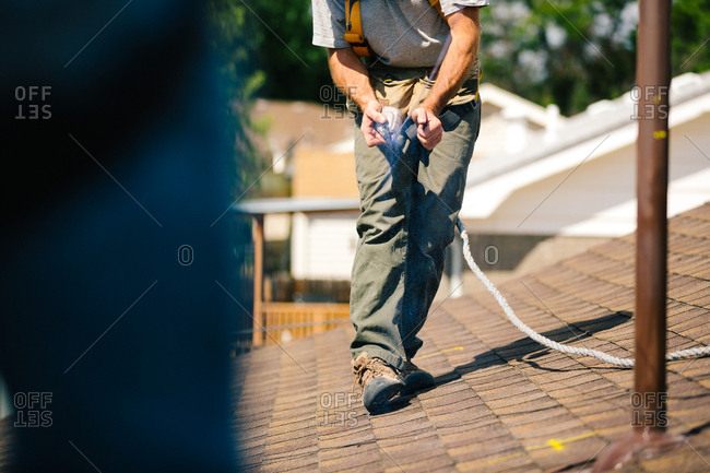 Man using chalk line to mark roof for solar panel installation