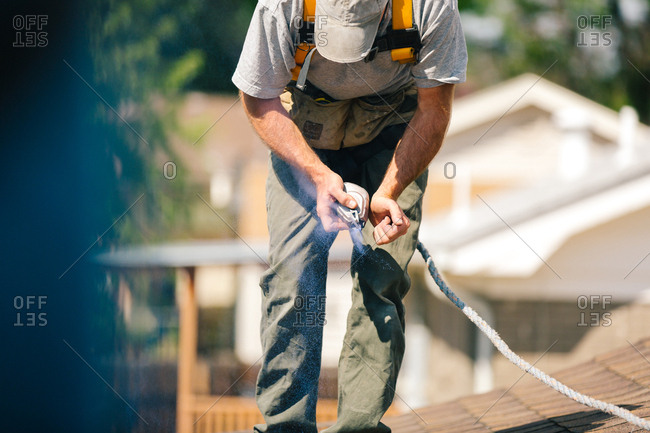 Man shaking a chalk line tool on a roof