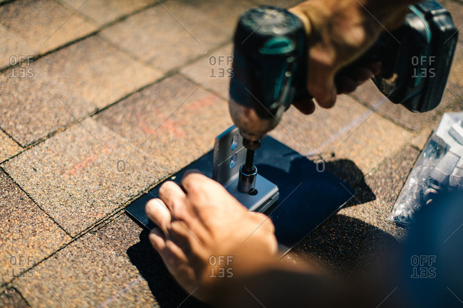 Construction worker installing component for solar panel installation