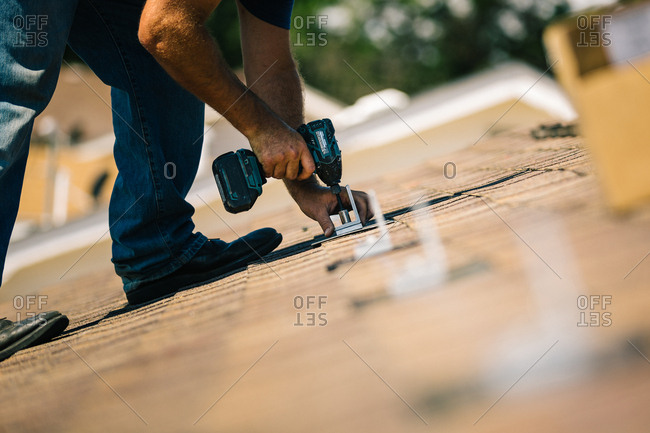 Man bolting brackets onto a roof for solar panel installation