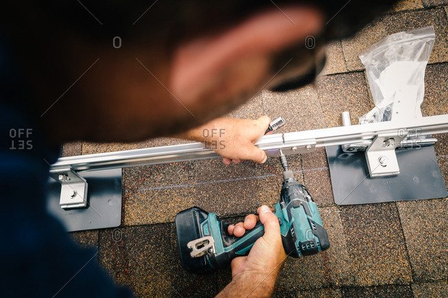 Construction worker screwing brackets together on a roof for solar panels