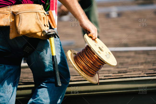 Construction worker carrying copper wire on a roof
