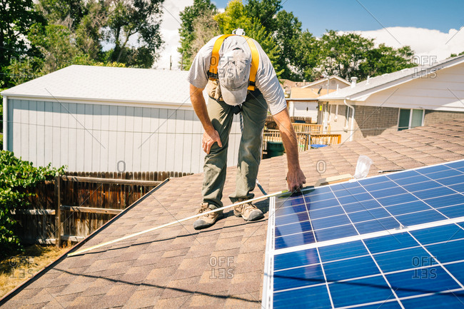 Man using tape measure while installing solar panels