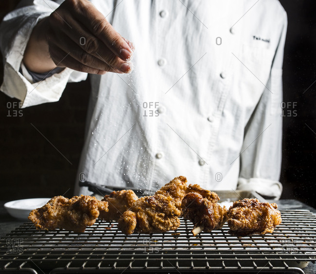 Chef sprinkling salt on fried chicken