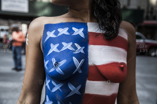 Times Square, New York, USA - September 19, 2014: Cropped view of a topless adult woman with an expression of the American flag painted on her chest