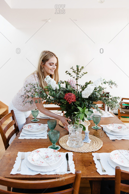 Young woman placing flowers in the center of a table setting at home