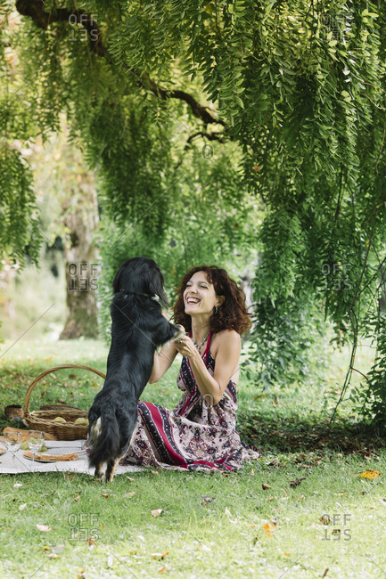 Woman with dog having a picnic in a park