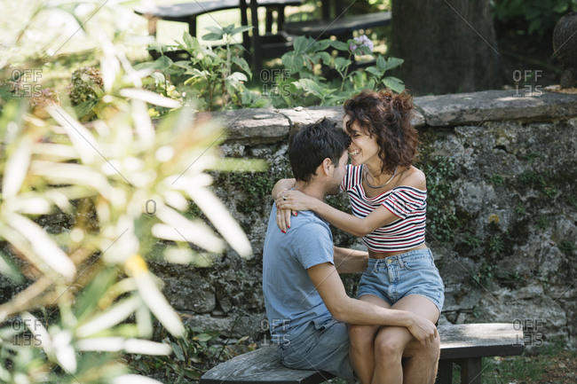Couple in love hugging on bench in a park