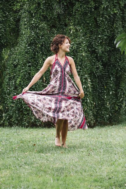 Happy woman in a park wearing summer dress