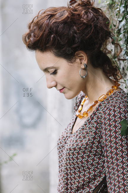 Woman wearing elegant dress leaning against a wall