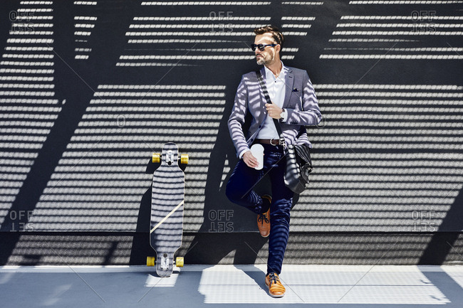 Businessman with longboard and coffee leaning against wall