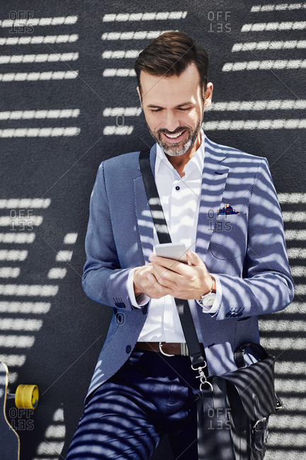 Portrait of businessman with longboard and phone near concrete wall