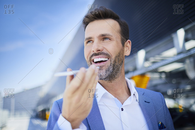 Portrait of cheerful businessman with phone in the city