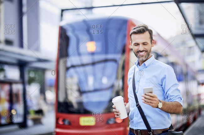 Businessman using phone after getting off public transport