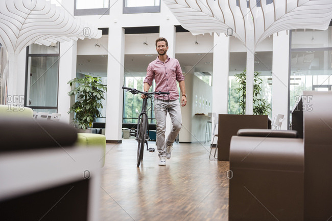 Man with bicycle walking in office