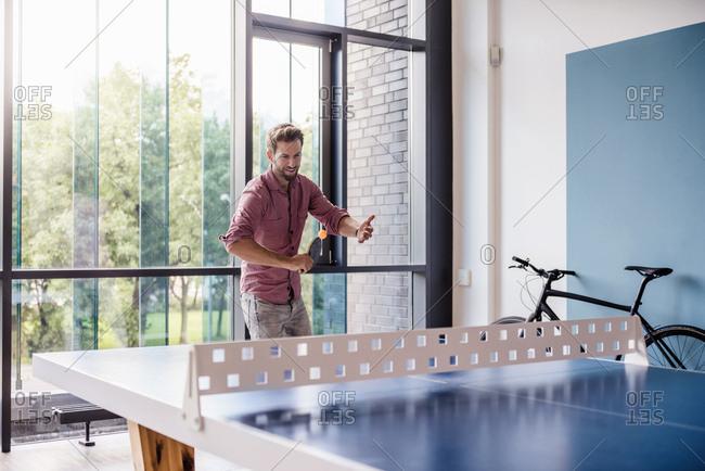 Man in break room of modern office playing table tennis