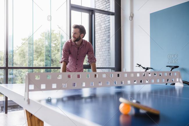Man in break room of modern office at table tennis table